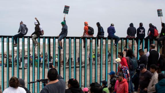 Central American migrants traveling with a caravan gather at the border wall, some sitting on top of it, look toward the U.S. from Mexico during a gathering of migrants living on both sides of the border, on the beach where the border wall ends in the ocean, in Tijuana, Mexico, Sunday, April 29, 2018. U.S. immigration lawyers are telling Central Americans in a caravan of asylum-seekers that traveled through Mexico to the border with San Diego that they face possible separation from their children and detention for many months. They say they want to prepare them for the worst possible outcome. (AP Photo/Hans-Maximo Musielik)
