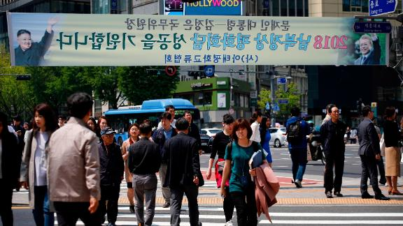 Seoul, SOUTH KOREA - APRIL 27: People walk under the placard celebrating Inter-Korean Summit in the street on April 27, 2018 in Seoul, South Korea. North Korean leader Kim Jong Un and South Korean President Moon Jae-in meets at the border today for the third-ever inter-Korean summit talks since the 1945 division of the peninsula. (Photo by Woohae Cho/Getty Images)