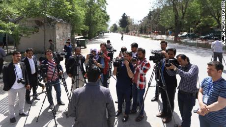 An official briefs journalists at the scene of the blasts in Kabul on Monday.