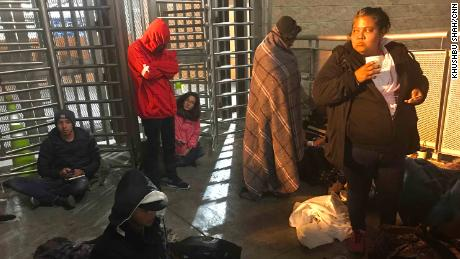 Migrants wait at the US-Mexico border to have their asylum claims processed. America lies on the other side of the turnstiles.