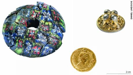 A large millefiori glass sword bead, a Valentinian III solidus (Roman coin) and a gilded silver sword pendant found on the floor of one of the homes.