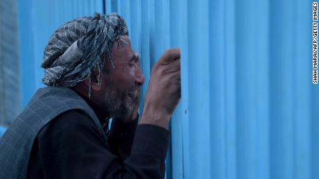 An Afghan man who lost his father in a 2016 attack targeting Shiite pilgrims weeps at the gate of Karte Sakhi shrine in Kabul.