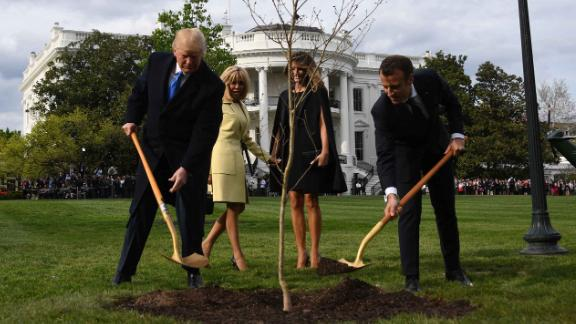 US President Donald Trump and French President Emmanuel Macron plant a tree watched by Trump