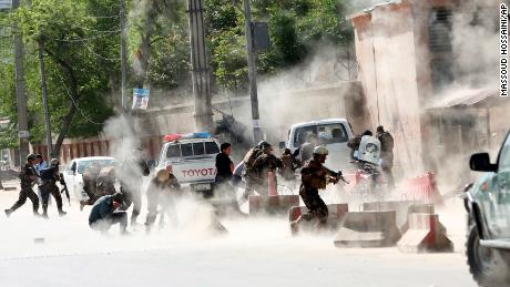 Security forces run from the site of an explosion in Kabul, Afghanistan,  April 30.