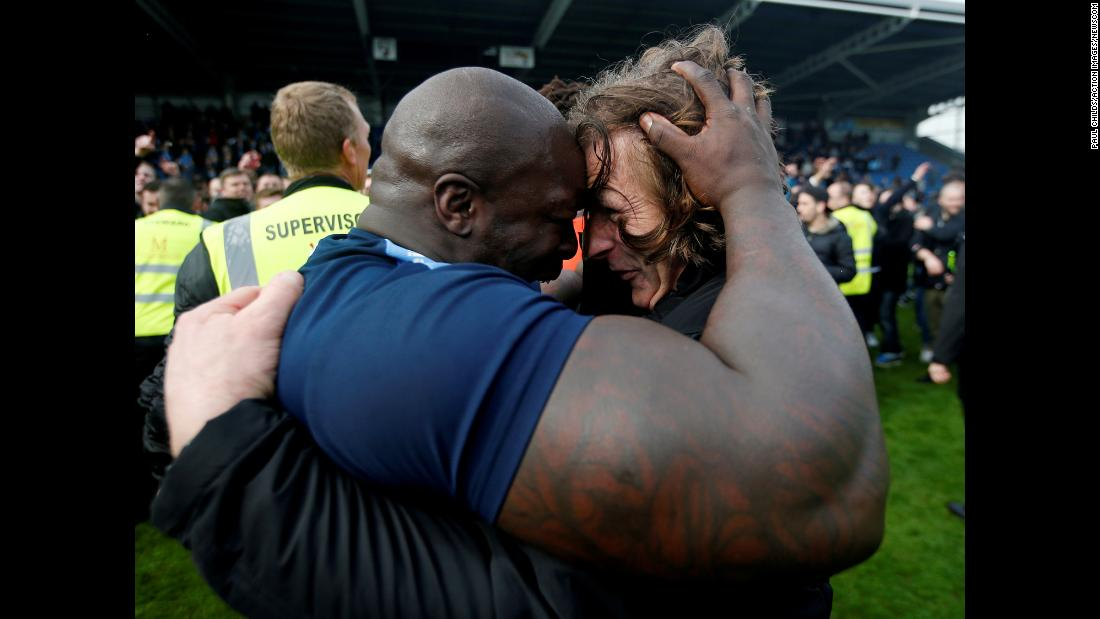 Wycombe Wanderers forward Adebayo Akinfenwa, left, celebrates with manager Gareth Ainsworth after the club won promotion to League One, the third tier of English professional soccer, on Saturday, April 28.