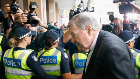 Police cordon off the media as Cardinal Pell walks into Melbourne Magistrates