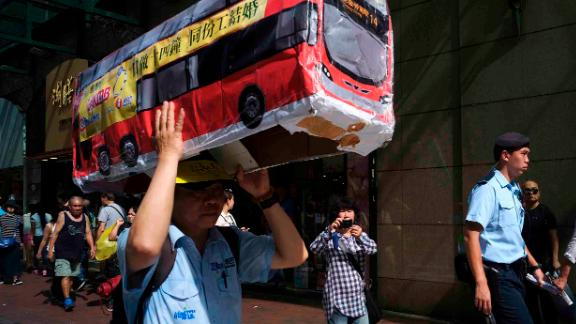 A protester raises a model of a bus, during a rally in Hong Kong calling for better labor conditions.