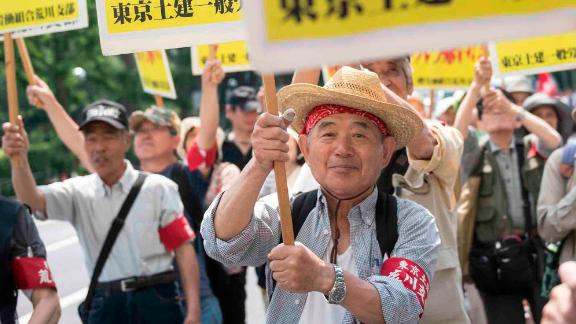 Workers hold placards at a rally organized by the Japanese Trade Union Confederation, in Tokyo.