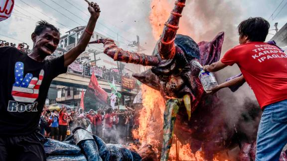 Workers burn an effigy of President Rodrigo Duterte as part of demonstrations outside the presidential palace in the capital Manila.