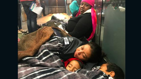 Migrants Tesla Rich, sitting, and Gabriela Hernandez, with sons Jonathan and Omar, try to keep warm as they await border officials to call them for asylum processing.