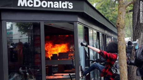 Activists smash windows of a McDonald's restaurant after it was hit with petrol bombs during a May Day rally in the center of Paris.