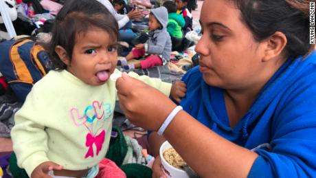 Catherine Enamorado feeds her 12-month-old daughter Ashly as they wait to present themselves to US border officials. Enamorado says she fled Honduras after gang members threatened to rape both her and her baby.