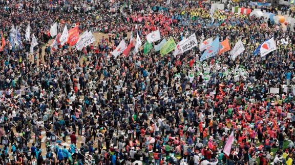 Members of the Korean Confederation of Trade Unions carry flags during a rally in Seoul.