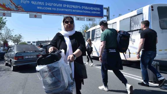 Passengers carry their luggage past protesters blocking a road to the airport on Wednesday.
