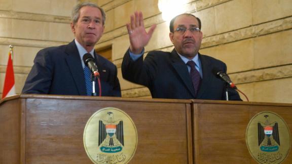 In a 2008 photo, Iraqi Prime Minister Nuri al-Maliki (R) tries to shield US President George W. Bush after an Iraqi man threw his shoes at Bush.