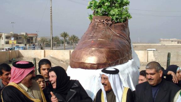 Iraqi officials share a laugh as they unveil a bronze shoe monument representing the one thrown by al-Zaidi at former US president George W. Bush.