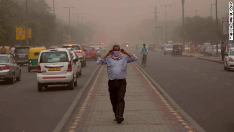 A man wraps a scarf around his nose as a dust storm envelops the city in New Delhi, India, Wednesday, May 2, 2018. (AP Photo/Manish Swarup)