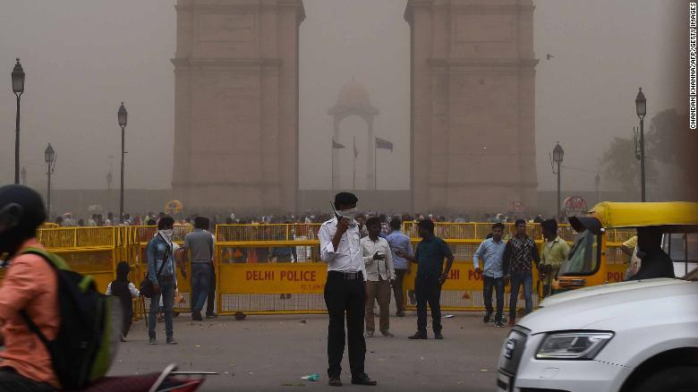 An Indian traffic policeman covering his face as he stands on duty during a dust storm in New Delhi on May 2.