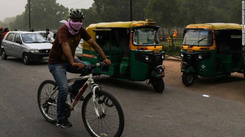 A man covers his face as he cycles during a dust storm in New Delhi, May 2.