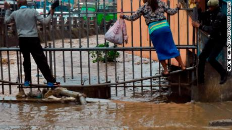 Pedestrian use a metal fence to cross, as they wade through the flooded road on their way to work following heavy rainfall, on March 15, 2018 in Nairobi.