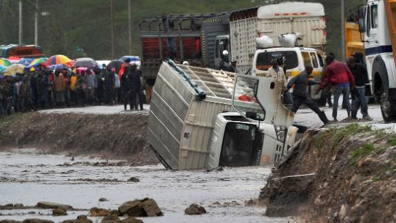 A man climbs off a truck that was washed off a road by flash floods in Isinya, about 58 km southeast of Nairobi, on March 15, 2018.