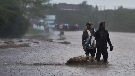 People wade across a flooded highway in Kajiado county, about 36 miles southeast of Nairobi, on March 15, 2018.