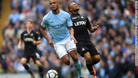 MANCHESTER, ENGLAND - APRIL 22:  Vincent Kompany of Manchester City runs with the ball whilst Jordan Ayew of Swansea City reacts during the Premier League match between Manchester City and Swansea City at Etihad Stadium on April 22, 2018 in Manchester, England.  (Photo by Laurence Griffiths/Getty Images)
