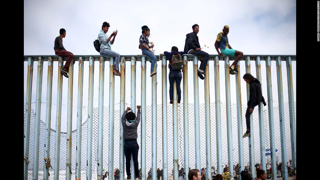 "Migrants climb a border fence in Tijuana, Mexico, as part of a demonstration on Sunday, April 29. A caravan of Central American migrants, traveling through Mexico for the past month, has started to reach the US border just outside of San Diego. There, they have begun applying for asylum. <a href=""https://www.cnn.com/interactive/2018/05/world/migrant-caravan-cnnphotos/"" target=""_blank"">In pictures: 2,000 miles with the migrant caravan</a>"