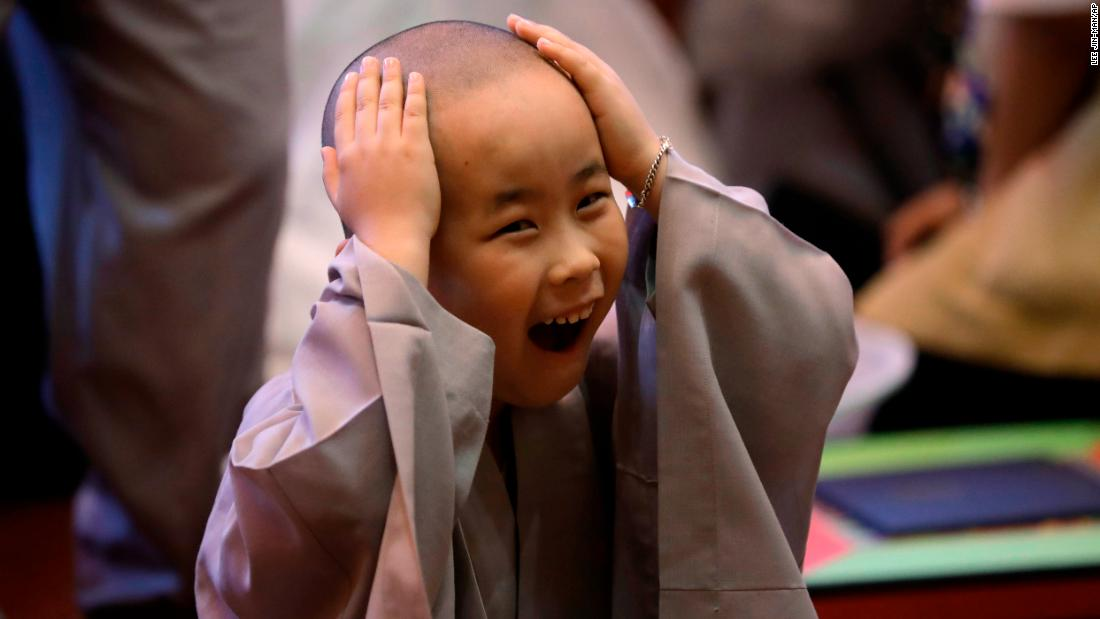 A boy touches his freshly shaved head on Wednesday, May 2, after he and nine other children entered the Jogye Temple in Seoul, South Korea, to experience what it's like to be a Buddhist monk.