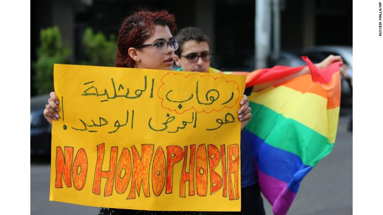 "Supporters of the LGBT community protest the criminalization of homosexuality outside a Beirut police station in 2016. The Arabic writing reads: ""The only disease is homophobia."""