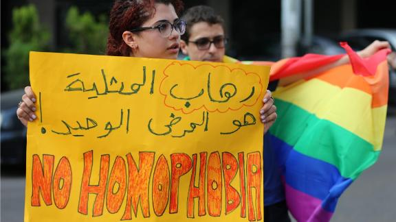 """Supporters of the LGBT community protest the criminalization of homosexuality outside a Beirut police station in 2016. The Arabic writing reads: """"The only disease is homophobia."""""""