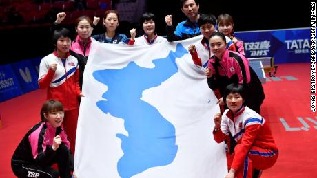 Staff members and players from both South Korea and North Korea pose with a flag.