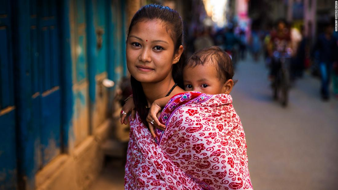 "<strong>Kathmandu, Nepal:</strong> A Hindu mother carries her boy. ""I remember that she was extremely tiny and had this baby face,"" said photographer Mihaela Noroc, recalling this older photo in a telephone interview from South Korea. ""I asked if she was married, and she said yes. I think she was very young."""