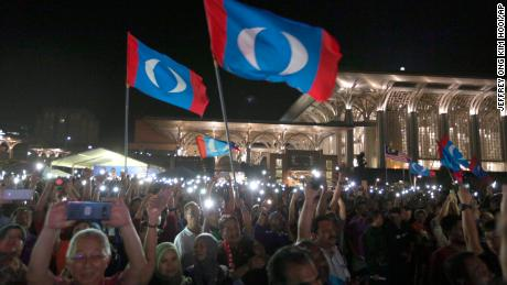 Supporters wave opposition party flags during an election campaign rally organized by Mahathir Mohamad, Putrajaya, Malaysia, May 3.