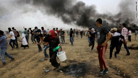 Palestinian protesters run for cover from teargas fired by Israeli troops during a protest at the Gaza Strip's border with Israel, east of Khan Younis, Friday, May 4, 2018.