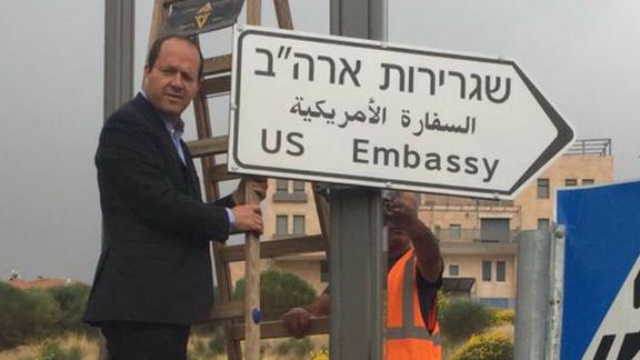 Jerusalem Mayor Nir Barakat poses next to the newly erected road sign.
