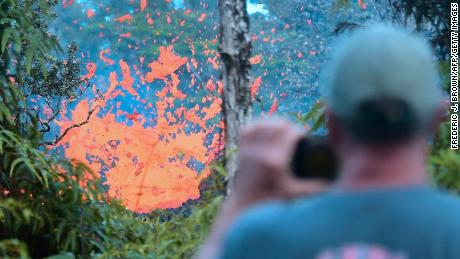 TOPSHOT - A man watches as lava is seen sewing from a fissure in the Leilani Estates subdivision near the town of Pahoa on Hawaii's Big Island on May 4, 2018 as up to 10,000 people were asked to leave their homes following the eruption of the Kilauea volcano that came after a series of recent earthquakes. (Photo by Frederic J. BROWN / AFP)        (Photo credit should read FREDERIC J. BROWN/AFP/Getty Images)
