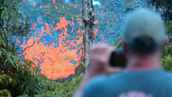 A man watches as lava spews from a fissure in the Leilani Estates subdivision near Pahoa, Hawaii.