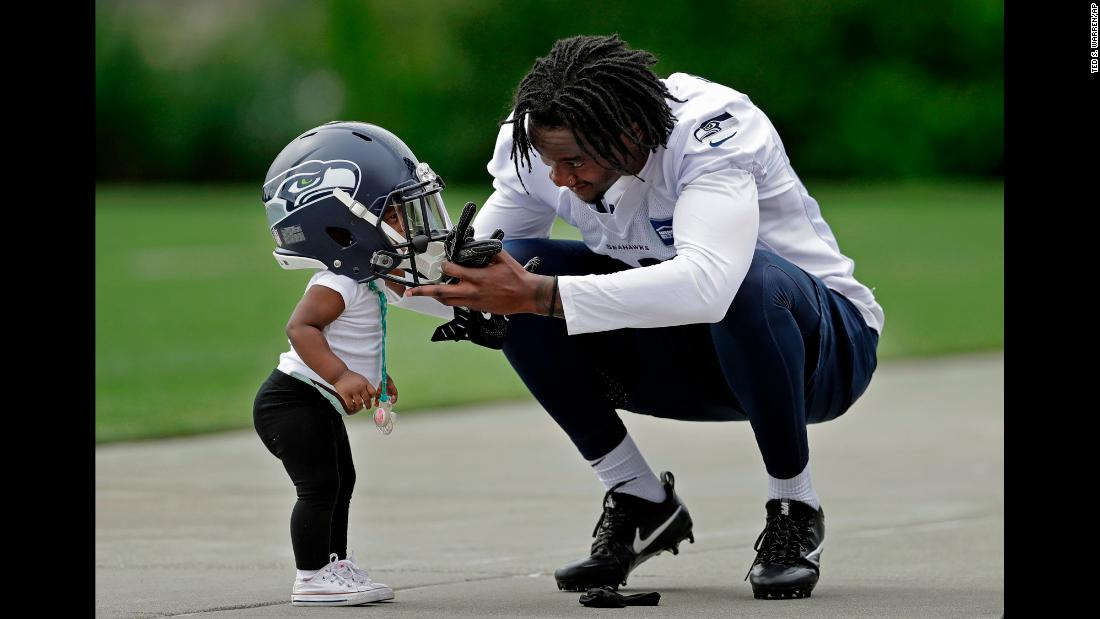 Seattle cornerback Tre Flowers puts his helmet on his 1-year-old daughter, Bailee, after attending rookie camp on Friday, May 4.