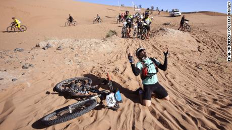 TOPSHOT - A competitor reacts after crossing a sand dune during Stage 4 of the 13th edition of the Titan Desert 2018 mountain biking race between Boumalne Dades and Merzouga in Morocco on May 2, 2018. - The Titan Desert 2018 is 600 kilometre mountain bike race completed over six days, snaking between Boumalne Dades, at the foot-slopes of the High Atlas summits, and Erfoud, an oasis town in the Sahara Desert. (Photo by FRANCK FIFE / AFP)        (Photo credit should read FRANCK FIFE/AFP/Getty Images)