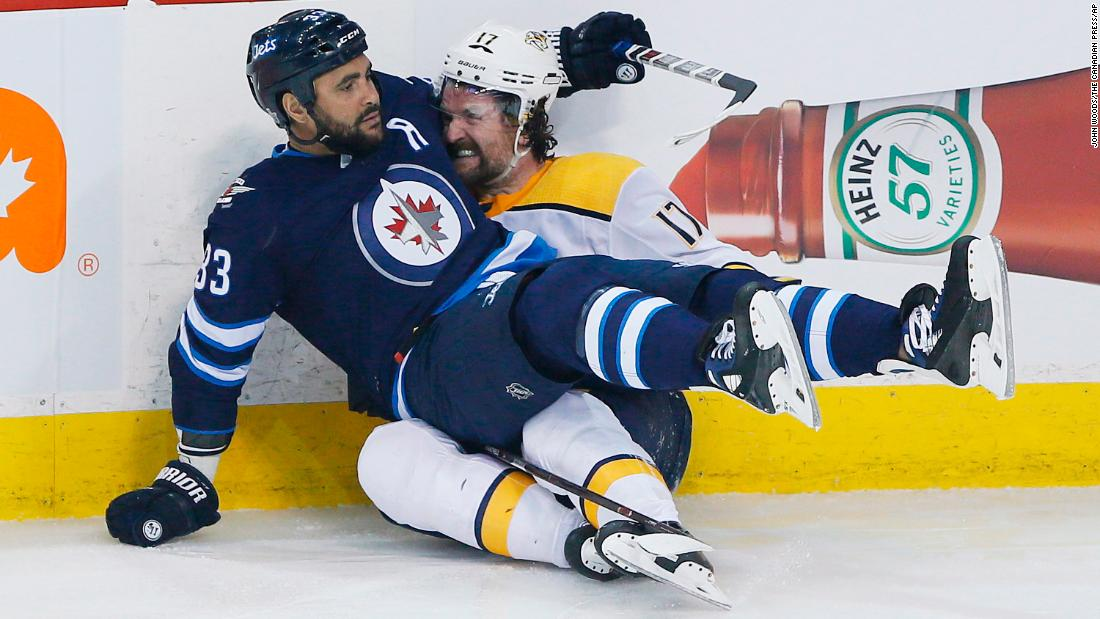 Winnipeg's Dustin Byfuglien, left, and Nashville's Scott Hartnell become better acquainted after colliding during Game 4 of their NHL playoff series on Thursday, May 3.