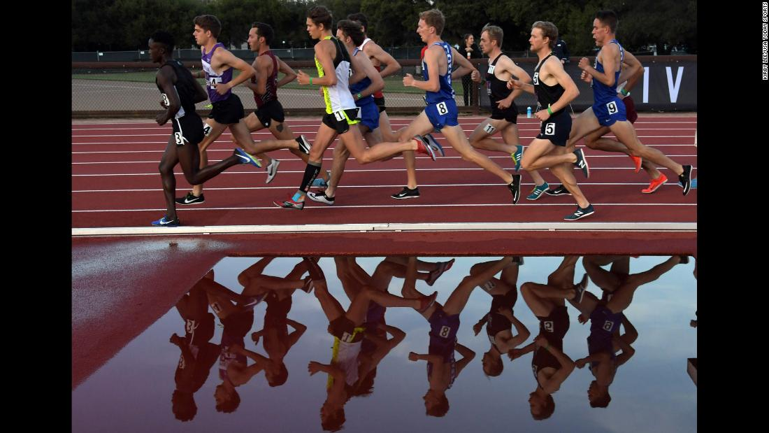 Collegiate runners are reflected by a water obstacle during a race in Stanford, California, on Thursday, May 3.