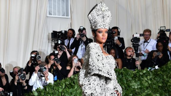 Rihanna dons a pope-inspired ensemble, including a jeweled miter. The singer co-chaired the event with Anna Wintour, Donatella Versace and Amal Clooney.