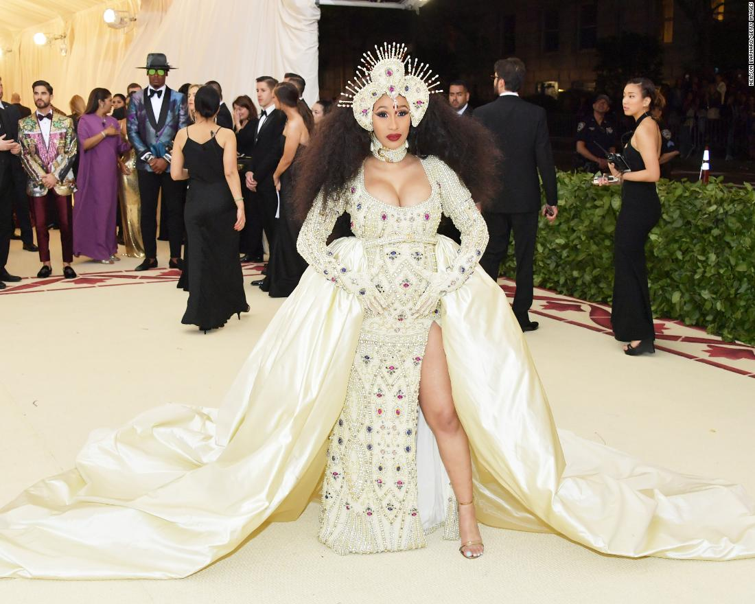 Cardi B wears an intricate headpiece and shimmering gown and train. She was joined by designer Jeremy Scott on the carpet. <br />