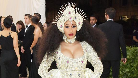 Cardi B wears an intricate headpiece and shimmering gown and train. She was joined by designer Jeremy Scott on the carpet.