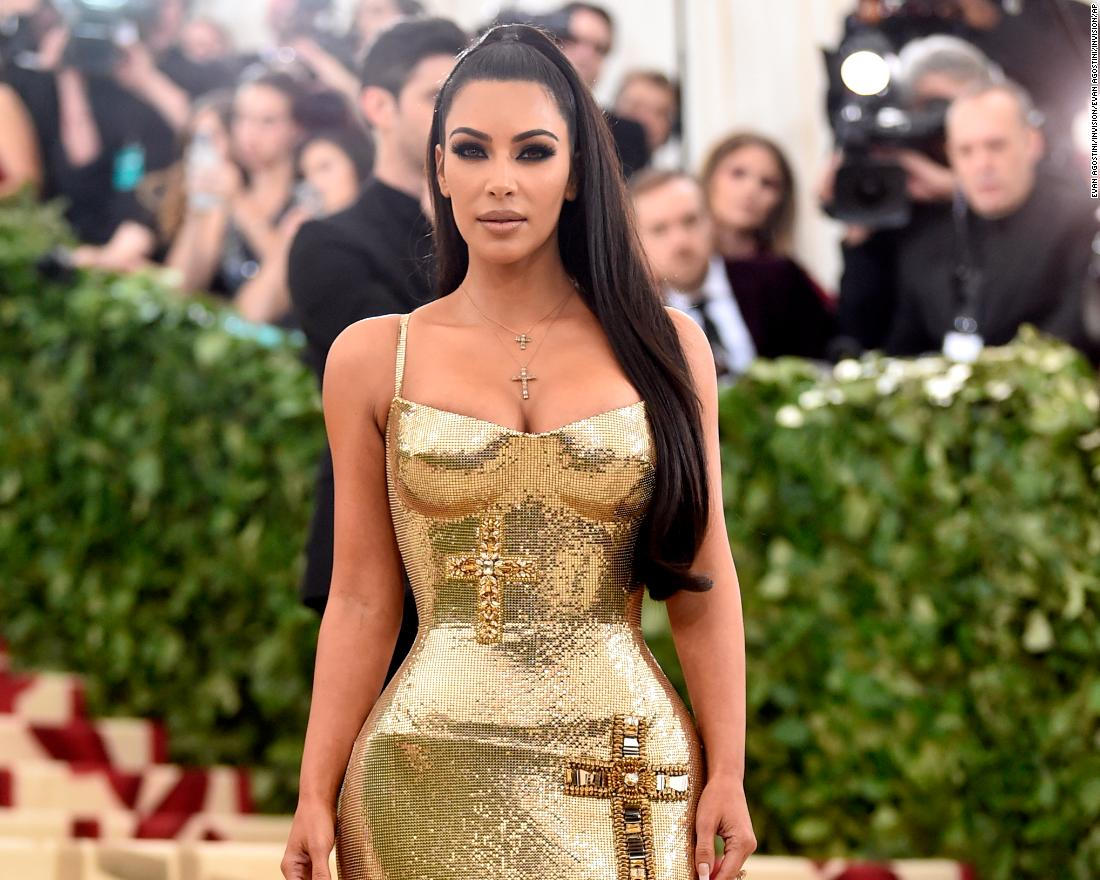 Kim Kardashian shows off a form-fitting dress with embroidered crosses.