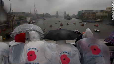 Spectators watch through the driving rain as hundreds of boats make their way down the River Thames for the Queen's Diamond Jubilee celebrations in London,Sunday, June  3, 2012.
