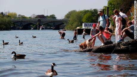 People soak up the sun and play in the shallows of the River Thames in Richmond, south west London, on May 7.