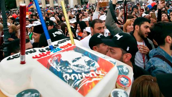 Supporters of Pashinyan carry a cake showing his face at a gathering in central Yerevan Tuesday.