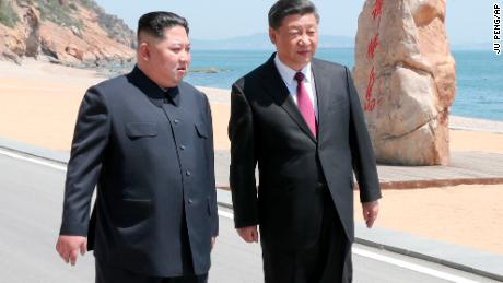 Chinese President Xi Jinping, right, walks with North Korean leader Kim Jong Un during a meeting in Dalian in northeastern China.